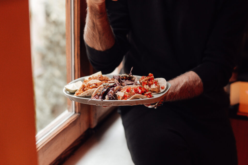 Man holding plate of tacos